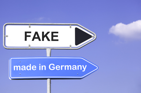 forfeiture: blue sky behind two road signs  on a metal mast with arrows to the right  side showing the way to Fake made in Germany. Concept for the  nitric oxide emission crisis of turbo diesel engines