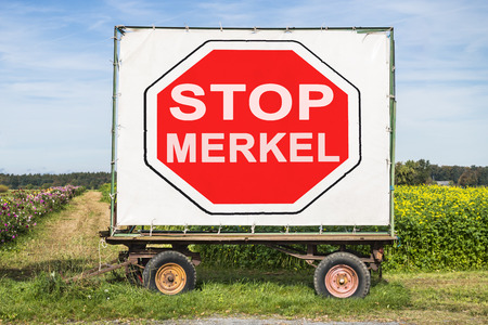 opposition: rural landscape with field, trailer and a stop sign with the words Stop Merkel. Concept for the growing political opposition against german chancellor Angela Merkel in the refugee crisis Stock Photo