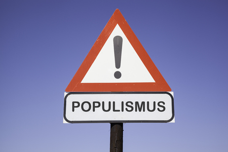 White road warning triangle with black  exclamation point and red frame on  a wooden mast in front of a blue sky. A second rectangular sign warns in english about populism in german