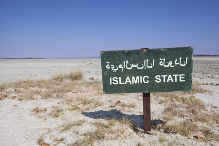 arabische letters: green sign in the desert with the words islamic state in english and arabic letters. Political concept concerning terrorism and the war in Syria and Iraq