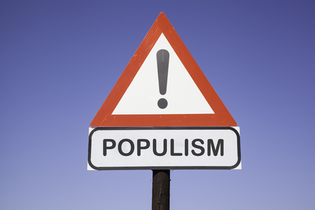 White road warning triangle with black  exclamation point and red frame on  a wooden mast in front of a blue sky. A second rectangular sign warns in english about populism