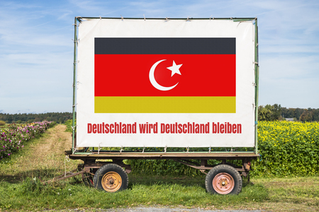 trailer with a german and turkish flag and the words Germany will remain Germany in german. Concept concerning the refugee and government crisis, immigration policy, german and turkish relationship Фото со стока