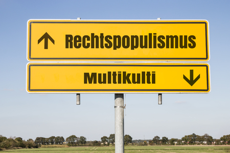 rightwing: yellow german traffic sign with the german words for right-wing populism and and multiculti. Arrows showing uptrend and downtrend. Concept concerning the growing nationalism and xenophobia Stock Photo