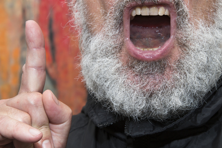 preachment: open mouth of an elder black dressed man with a grey full beard and a raised forefinger, concept for religious preachment and the power or danger of words Stock Photo