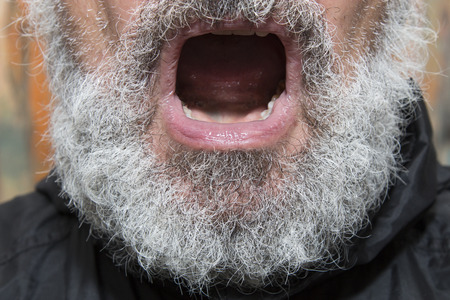 preachment: black dressed elder man with a grey full beard and open mouth, concept for religous preachment and the power or danger of words