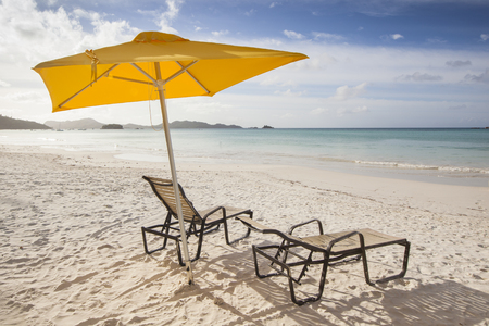 yellow sunshade with two sunbeds at a beach in summer. Tourism concept for travel, vacation and holidays.