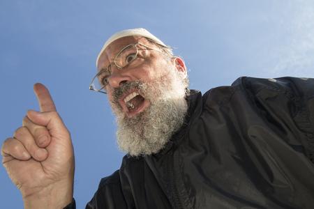 gatillo: vestido negro musulmán anciano con barba y takke hablar con el dedo en gatillo levantado
