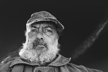 retrato en blanco y negro de un viejo vagabundo con la barba completa, la tapa y el escudo desigual