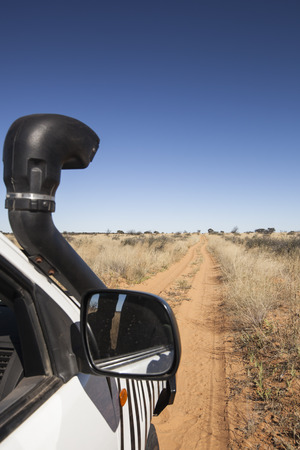 off road car on a red Kalahari desert trail, Botswana, Africa; concept for adventure and travel