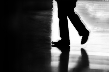 Black silhouette of the legs of a man stepping from the light  into the dark Editorial