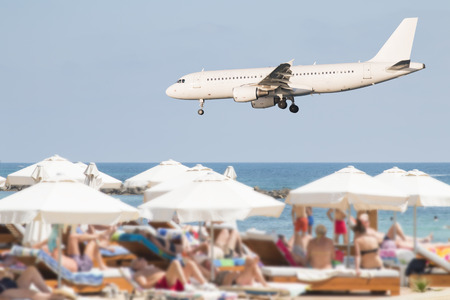 Landing airplane over a crowded beach with white sunshades, concept for summer vacation and mass tourism Editorial