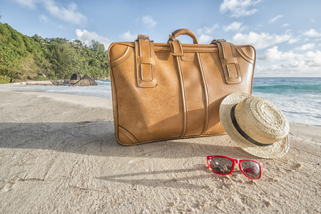 Vintage brown suitcase with a straw sunhat and sunglasses at a beautiful tropical beach. Concept for travel, tourism and summer vacation; Mahe Island, Seychelles, Africa,
