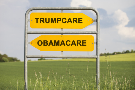 Two yellow signs with arrows and the words Trumpcare and Obamacare showing in different directions, political concept for american health care