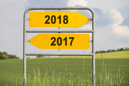 two yellow direction signs with arrows and the numbers 2017 and 2018, concept for turn of the year
