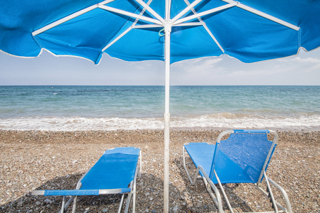 two blue sunbeds under a blue sunshade at the beach, concept for summer, travel and vacation, latsi beach, cyprus island, Europe Stock Photo