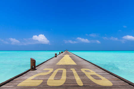 wooden jetty with the word 2018 and an yellow arrow showing forward to the horizon, business concept for turn of the year Stock Photo