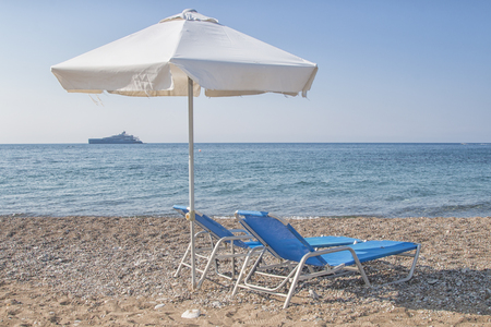 white sunshade and blue sunbeds at pebble beach with a luxury yacht at the horizon, Latsi beach, Cyprus, Greece, Europe