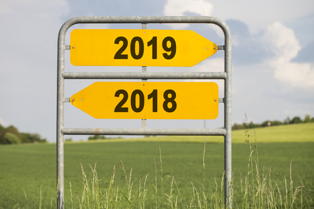 two yellow direction signs with arrows and the numbers 2018 and 2019, concept for turn of the year
