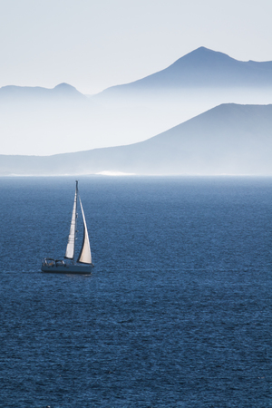 sea with sailboat and mountains of an island in haze, concept for travel, water sports and vacation, Lanzarote, canary islands, Spain, Europe