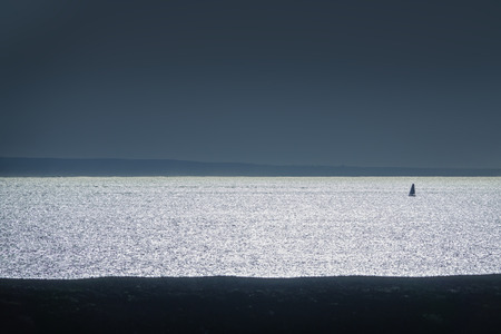 travel background in backlight with silhouette of a lonely sailboat on a reflecting ocean, Lanzarote, canary islands, Spain, Europe Banco de Imagens