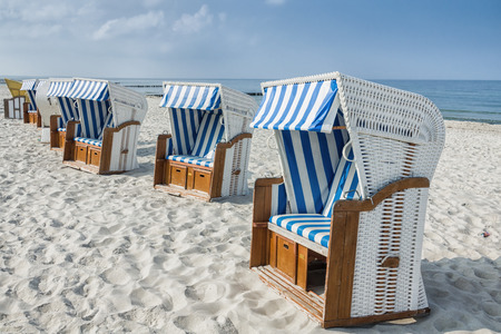 row of empty roofed wicker beach chairs in white sand  at baltic sea, Germany, Europe