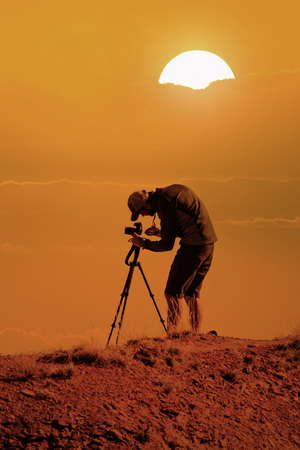 photographer with camera on tripod taking landscape pictures from mountain peak at sunset 免版税图像
