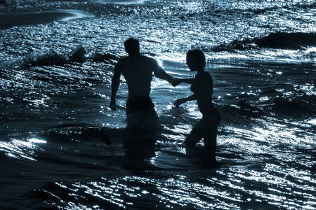 silouhettes of a woman and man holding hands while bathing in the sea, concept for togetherness, love and helping each other