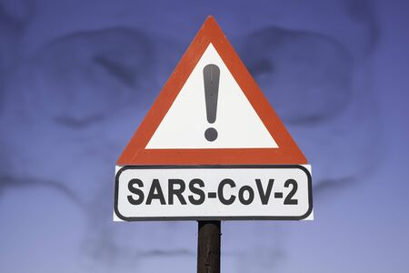 White road warning triangle with black  exclamation point and red frame on  a wooden mast in front of a blue sky. A second rectangular sign warns about  SARS-COV-2 virus epidemic or pandemic Standard-Bild