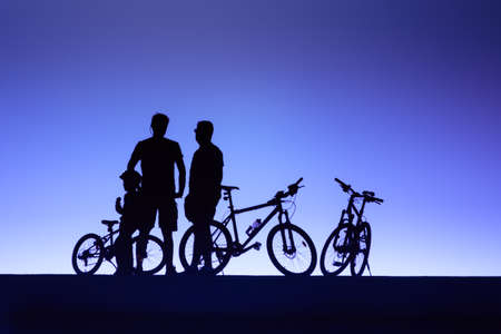 sporting background with the silhouettes of two men and a child with mountain bikes in front of a dark blue sky