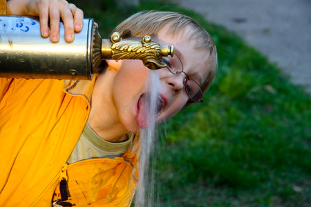 little boy greedily drinking water from the tap photo