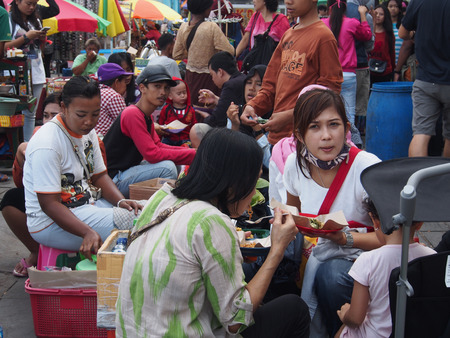 sidewalk talk: JAKARTA- INDONESIA JANUARY 11, 2015. The local  market, with colourfully dressed people. On the site, people sitting on chairs and eating  meals purchased on the market.