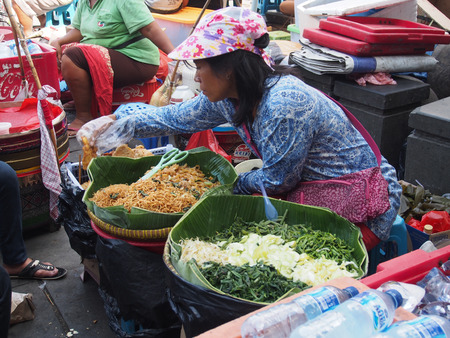colourfully: JAKARTA- INDONESIA JANUARY 11, 2015. The local  market, with colourfully dressed people. On the site, people sitting on chairs and eating  meals purchased on the market.