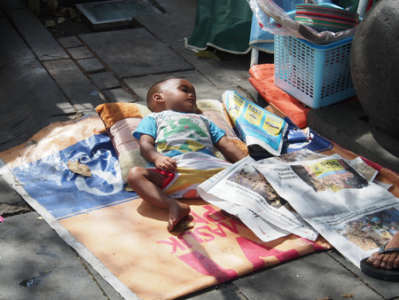 sidewalk talk: JAKARTA- INDONESIA JANUARY 11, 2015.The local market. Mother put her toddler to sleep on the ground next to her stand and covered it with newspapers.