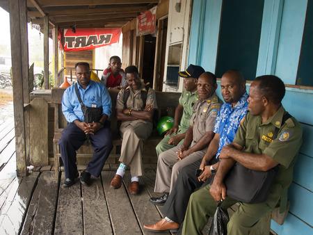 cornrows: Dekai, Indonesia - 12 de enero de 2015: Los oficiales de polic�a locales vestidos con uniformes y hombres civiles sentarse y descansar en frente de un bar