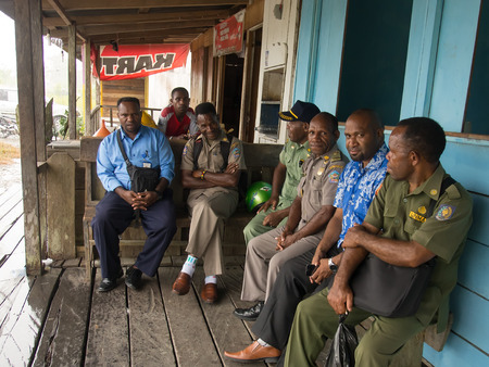 cornrows: Dekai, Indonesia - January 12, 2015: Local Police officers wearing uniforms and civilian men sitting and resting in front of a bar Editorial