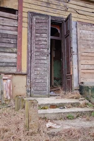 beroofd: Een oude vervallen houten deur geopend