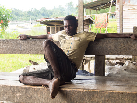 cornrows: Dekai, Indonesia - January 13, 2015: Local man sitting on a bench outside a bar