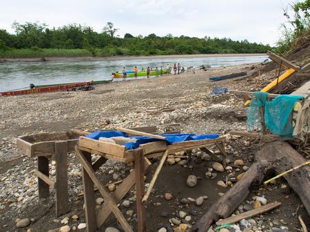 prospector: Jungle, Indonesia - 13 de enero 2015: Un pequeño estructuras compactas con tableros servir lugareños para vaciar oro de la arena de río