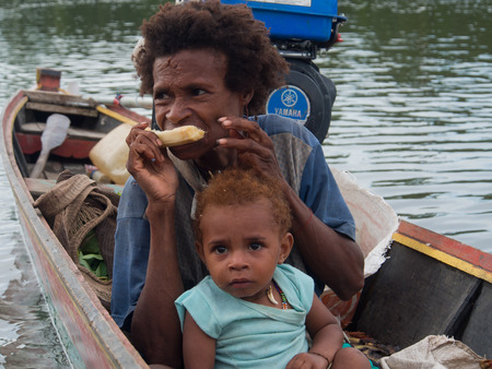 sidewalk talk: Jungle, Indonesia - January 13, 2015: A woman from the Korowaya tribe with a small child sitting in the boat when crossing  the river Editorial