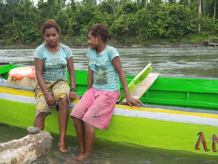 sidewalk talk: Jungle, Indonesia - January 13, 2015: Women of the Korowaya tribe sitting on the side of the boat Editorial