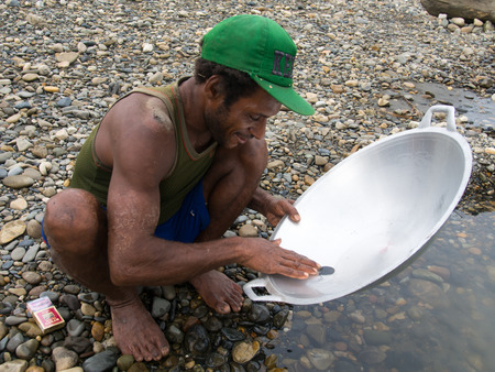 gold rush: Jungle, Indonesia - January 13, 2015: A man from the Korowaya tribe washing out  gold using a bowl