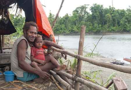 babysit: Jungle, Indonesia - January 13, 2015: A man from the Korowaya tribe with a child on his lap, sitting on the bank of the river fishing