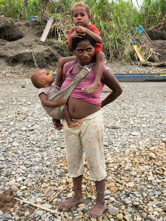 sidewalk talk: Jungle, Indonesia - January 13, 2015: A woman from the Korowaya tribe with two children on the banks of the river is preparing to washing our gold Editorial