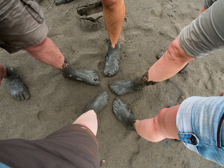 mud pit: Tourists with feet covered with  mud when leaving the boat