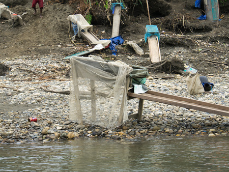 gold rush: Jungle, Indonesia - January 13, 2015: A small compact structures with boards serve locals to wash out gold from the river sand Stock Photo