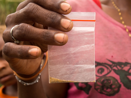 sidewalk talk: Jungle, Indonesia - January 13, 2015: A woman from the Korowaya tribe shows  gold particles Stock Photo