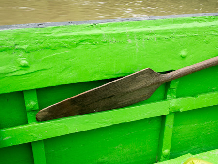 kayaker: Wooden paddle leaned against  the  side of the boat when sailing