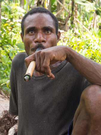 cornrows: The jungle, Indonesia - January 14, 2015: man smokes a cigar while crossing the jungle