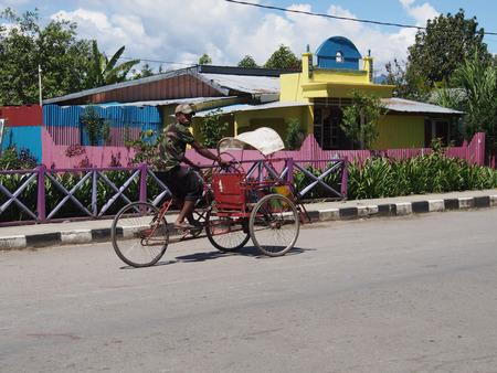 rikscha: Wamena, Indonesien - 23. Januar 2015: Ein Rikschafahrer. Junge, dunkle Haut Junge warten auf einen Client auf der Straße von Wamena