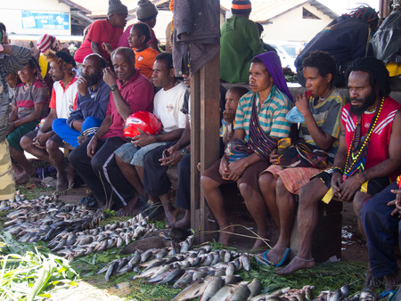 entrap: Wamena, Indonesia - January 23, 2015: Residents of Wamena on the street selling freshly caught fish arranged on the leaves of palm trees.